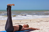 Woman doing yoga exercise reclined staff posture on beach — Stock Photo