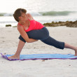 Woman on beach at sunset doing yoga exercise bound extended side angle pose — Stock Photo #6161625