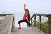 Woman doing yoga exercise warrior 1 pose on boardwalk at beach d — Stock Photo