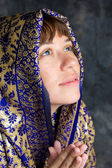 Beautiful woman smiling with shawl on head looking up and praying — Stock Photo