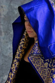 Mystical woman in blue and gold cape with hood — Stock Photo