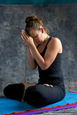 Woman praying on mat with mala beads — Stock Photo