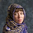 Sad looking woman wrapped in shawl — Stockfoto