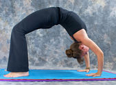 Woman doing yoga exercise full wheel pose on on mat in studio — Stock Photo