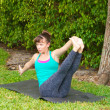 Woman doing Yoga pose Navasana variation or boat pose outdoors o - Stock Photo