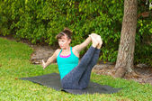 Woman doing Yoga pose Navasana variation or boat pose outdoors o — Stock Photo