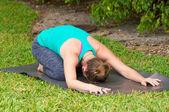 Woman doing Yoga posture Balasana or childs pose outdoors on gra — Stock Photo
