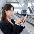 Young business woman using touch pad in the train station — Stock Photo