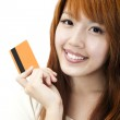 Portrait of the beautiful happy girl holding a credit card for shopping — Stock Photo