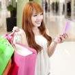 Young woman holding mobile phone and shopping bag in the mall — Stock Photo