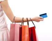 Hand of woman holding shopping bags and credit card — ストック写真