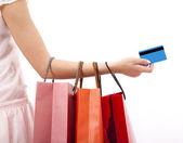 Main de femme tenant des sacs à provisions et carte de crédit — Photo