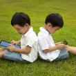 Royalty-Free Stock Photo: Two kids using touchscreen tablet PC on the grass