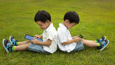 Two kids using touchscreen tablet PC on the grass — Stock Photo