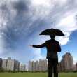 Businessman in dark suites with umbrella and watching storm — Stock Photo