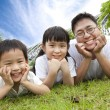 Happy family lying on the grass.father with son and daughter — ストック写真
