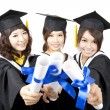 Three graduation asian girls holding their diploma — Stock Photo
