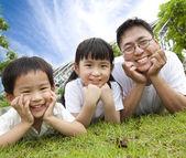 幸せな家族の息子と娘の grass.father に横たわっています。 — ストック写真