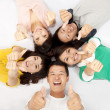Group of asian young lying together with thumb up — Stock Photo