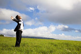 Young man in green field under blue skies — Stock Photo