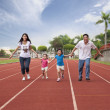 Happy asian family running together on the Stadium track — Stock Photo