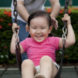 Laughing little girl on swing with her father — Stock Photo