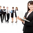 Smiling businesswoman holding laptop and successful business team — Stock Photo