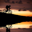 Silhouette of mountain biker with Reflection and sunset — Stock Photo