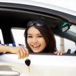 Young happy woman in car showing the keys — Stock fotografie