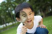 счастливый малыш с увеличительным стеклом — Стоковое фото