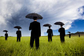 Businessman in black suit holding umbrella — Stock Photo