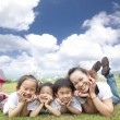 Happy asian family on the grass with cloud background — Stock Photo