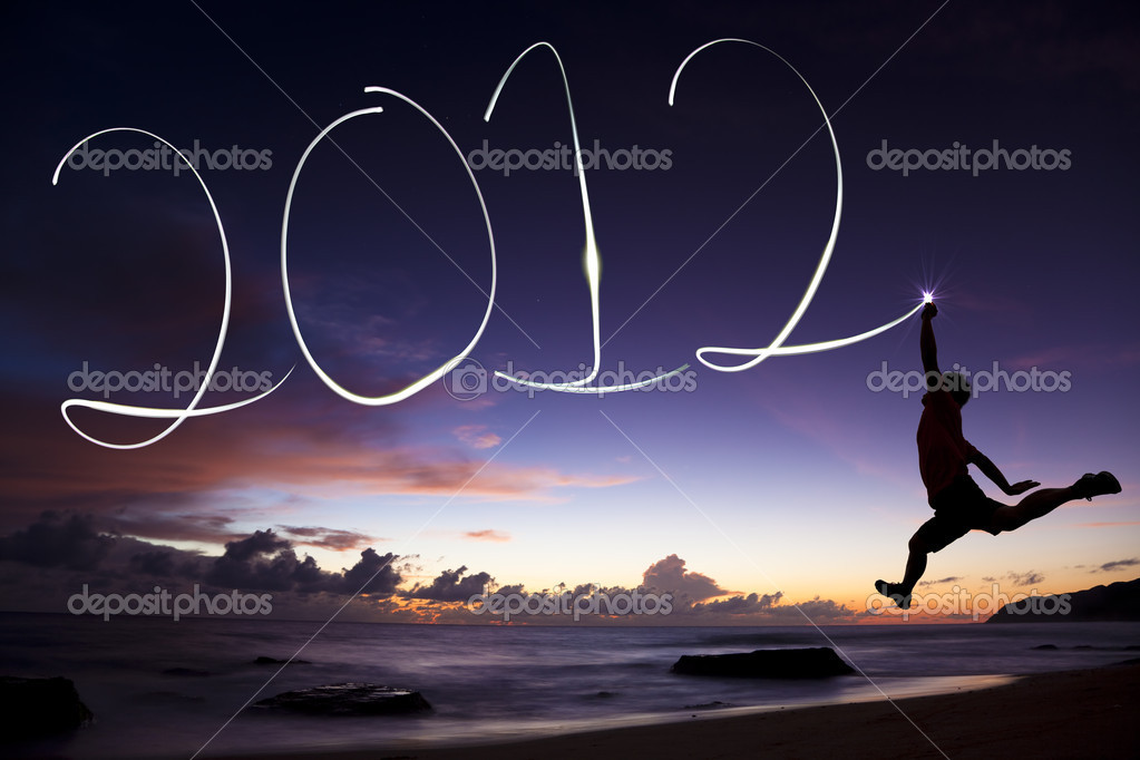 Happy new year 2012. young man jumping and drawing 2012 by flashlight in the air on the beach before sunrise — Stock Photo #6585817