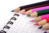 Colored pencils on notepad — Stock Photo