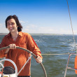Stock Photo: Young skipper driving sailboat