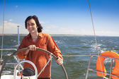 Young skipper driving sailboat — Stock Photo