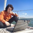 Businessman with laptop on sailboat — Stock Photo