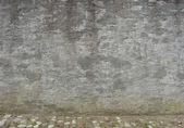 Old worn gray concrete wall with cobble street — Stock Photo