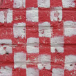 White and red paint checker pattern on brick wall — Stockfoto