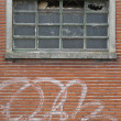 Stock Photo: Facade of abandoned building with broken windows and graffiti