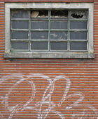 Facade of abandoned building with broken windows and graffiti — Stock Photo