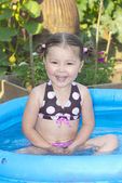 Happy little girl in a swimming pool — Stock Photo