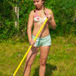 Young happy woman raking grass — Stock Photo