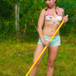 图库照片: Young happy woman raking grass