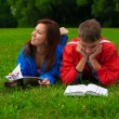 Two teenagers studying outdoors on grass — Stock Photo #6278484