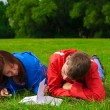 Two teenagers studying outdoors on grass — Stock Photo #6278594
