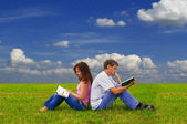 Two teenagers studying outdoors on grass — Stock Photo