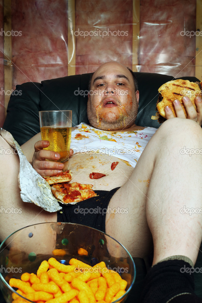 Photo of a fat couch potato eating a huge hamburger and watching television.  Harsh lighting from the television illuminates the dark room. — Stock Photo #5486612