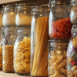 Dried pasta in jars on a shelf — Stock Photo