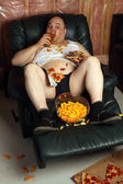 Hamburger eating lazy couch potato — Stock Photo